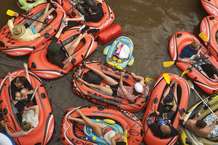 VANTAA, FINLAND  AUGUST 1, 2015: Beer Floating kaljakellunta, summer event, where the participants float down the Vantaa River using small rubber crafts and paddles.
