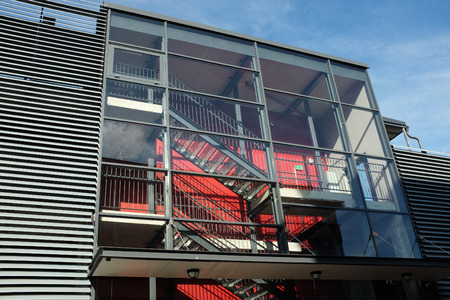 functionalism: glass stairwell of a modern building against blue sky