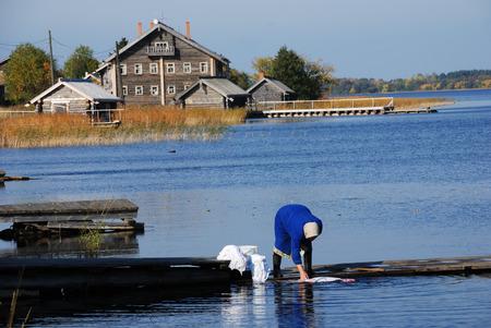 onega: JAMKA, RUSSIA, SEPTEMBER 24, 2008: resident fishing village rinsing linen in Lake Onega