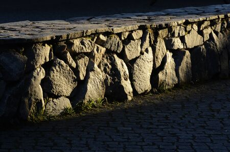candid: low stone wall and cobblestones in the sun