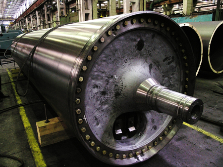 mechanical works: large metal shaft in the shop engineering plant