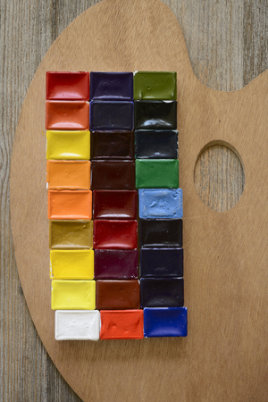 daubed: watercolor paint and palette on wooden background