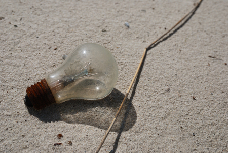 burned out: environmental pollution, burned out incandescent lamp on the beach