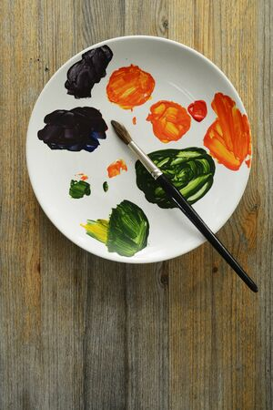 brush and paints on a white plate