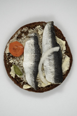 sliced herring on rye bread, white background