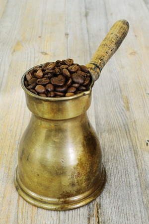 old arabic coffee pot on wooden background with beans Stock Photo
