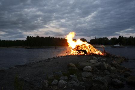 traditioneel vuur op de zomerzonnewende op de oever van het meer, Finland