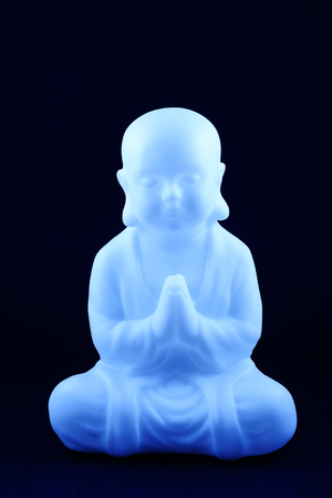 plastic blue buddha sculpture on the dark background