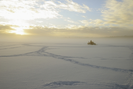 Snowmobile on a lake in a frosty foggy day