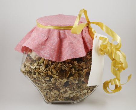 Muesli in a glass decorated jar on neutral background