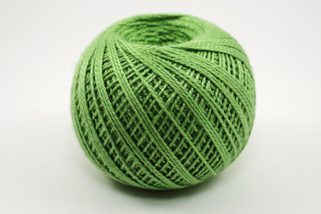 A skein of green wool on a white background