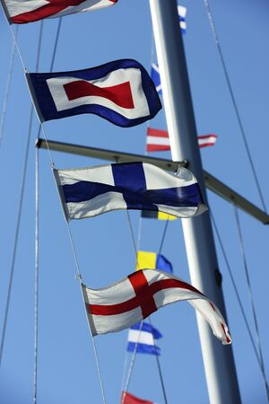 sea flags fluttering in the wind against a blue sky