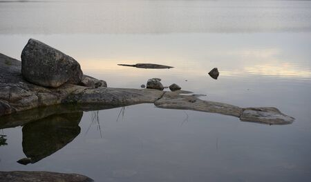 stones and rocky shore of the lake in Finland, sunset