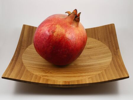 beautiful ripe red pomegranate on the wooden tray