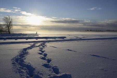 fog over winter lake in finland, sunset