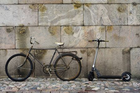 old vintage bicycle and scooter against a granite wall in Helsinki, Finland Banco de Imagens