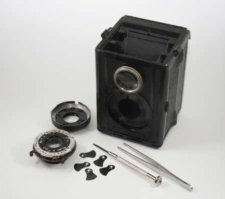 old vintage disassembled camera, screwdriver and tweezers, aperture blades Reklamní fotografie