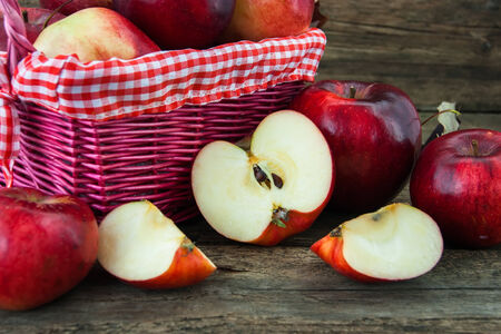 red apples in a basket on wooden background photo