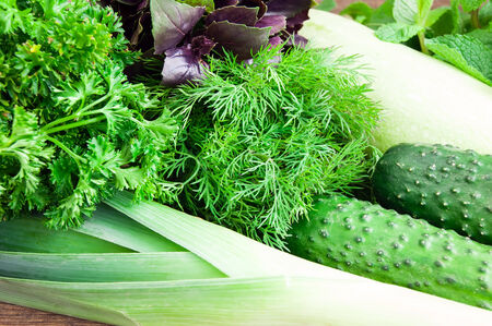 Fresh green vegetables on wooden table photo
