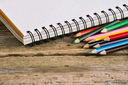 write letter: Checked blank notebook with multicolored pencils on wood background