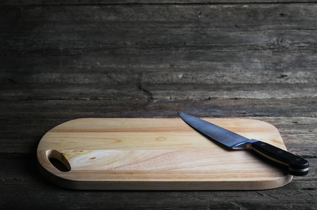 paring knife: Empty chopping board with a sharp paring knife on a distressed grunge wooden table in a rustic kitchen, overhead view with a vignette and copyspace Stock Photo