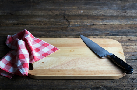 paring: Empty chopping board with a sharp paring knife and napkin on a distressed grunge wooden table Stock Photo