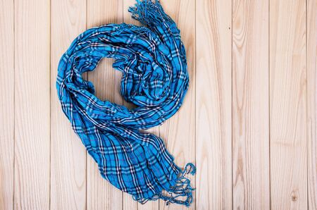 checkered scarf: blue checkered scarf on a wooden background