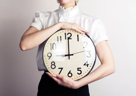 Business woman holding a clock Stockfoto