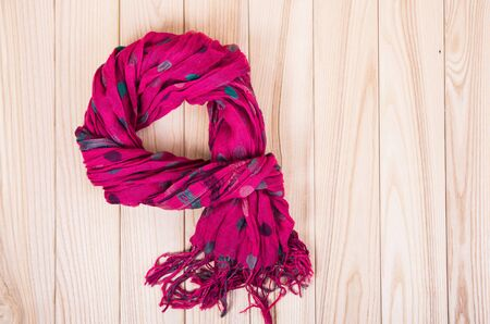 red scarf on wooden background Foto de archivo