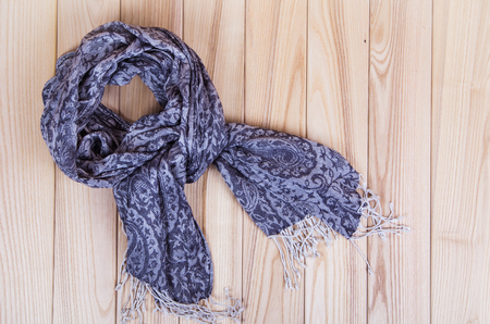 warm clothing: gray scarf on wooden background