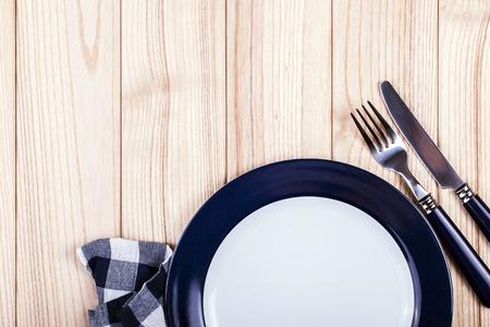 빈 접시, 나이프와 포크 및 나무 테이블에 파란색 냅킨