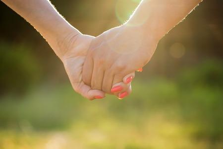 우정과 남자와 여자의 사랑의 개념 촬영 : 두 손을 통해 태양 광선과 자연