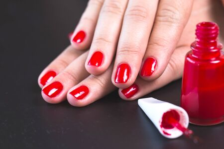 manicure and pedicure: red manicure with nail on a black background