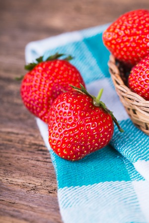 gardening: fresh strawberries in a bowl with checkered napkin on old wooden background Stock Photo
