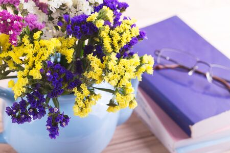 yellow tea pot: Flowers in teapot with books and glasses on a wooden background