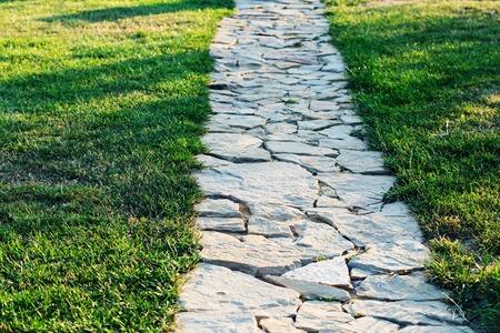 잔디와 정원 돌 경로는 돌 사이에 성장