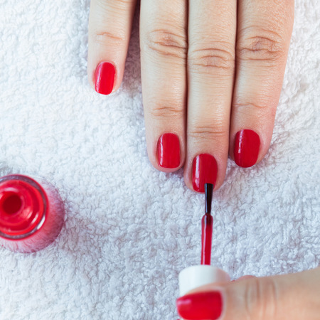 nails: Manicure - Beautiful manicured womans nails with red nail polish on soft white towel. Stock Photo