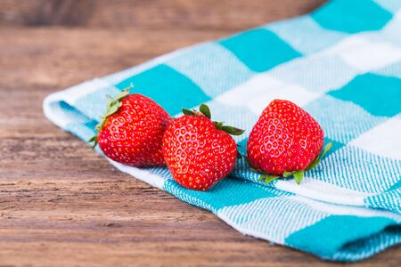 wooden basket: fresh strawberries in a bowl with checkered napkin on old wooden  Stock Photo