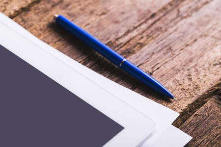 pen quality: Blank modern digital tablet with papers and pen on a wooden desk. Top view. High quality detailed graphic collage.