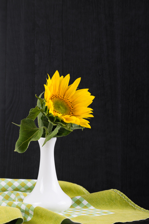 autumn grunge: sunflowers in a vase on a black background