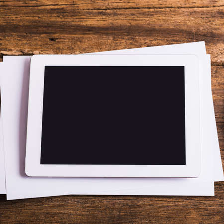 blank tablet: Blank modern digital tablet with papers and pen on a wooden desk. Top view. High quality detailed graphic collage.