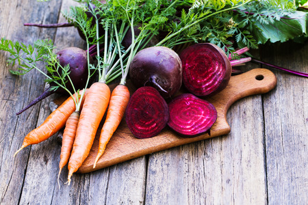 roots: Fresh beet and carrots on wooden background