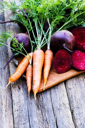 ensalada verde: La remolacha y la zanahoria fresca sobre fondo de madera