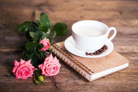 rosas rojas: cup of coffee with milk and pink roses and books on the old wooden background Foto de archivo