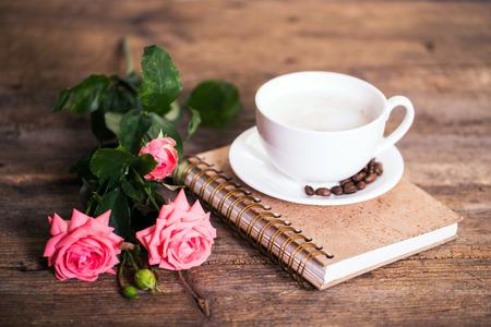 rosas rosadas: taza de caf� con leche y rosas rosas y libros en el fondo de madera vieja Foto de archivo