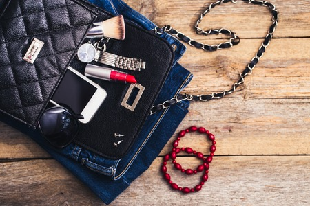 handbag: Fashion accessories for a young girl, watch, bracelet, handbag, red lipstick, telephone, brush on a wooden background. Stock Photo