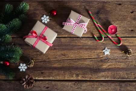 Christmas presents on a wooden background with candy cane, fir branches, candle, cones.