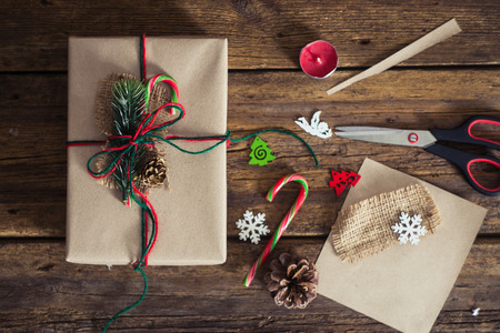 Christmas gift box on a wooden background with candy cane, fir branches, candle, cones.