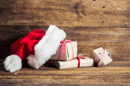 Christmas cards and gifts with Santa hats on wooden background with candy cane, fir branches, candle, cones. Stockfoto