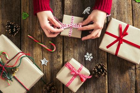 cajas navideñas: manos masculinas envolver los regalos de Navidad en papel y atarlos con hilos rojos